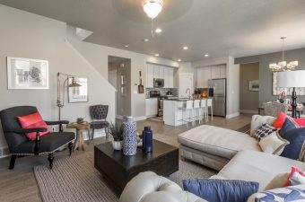 completed and furnished open-concept living room and kitchen built by McArthur Homes