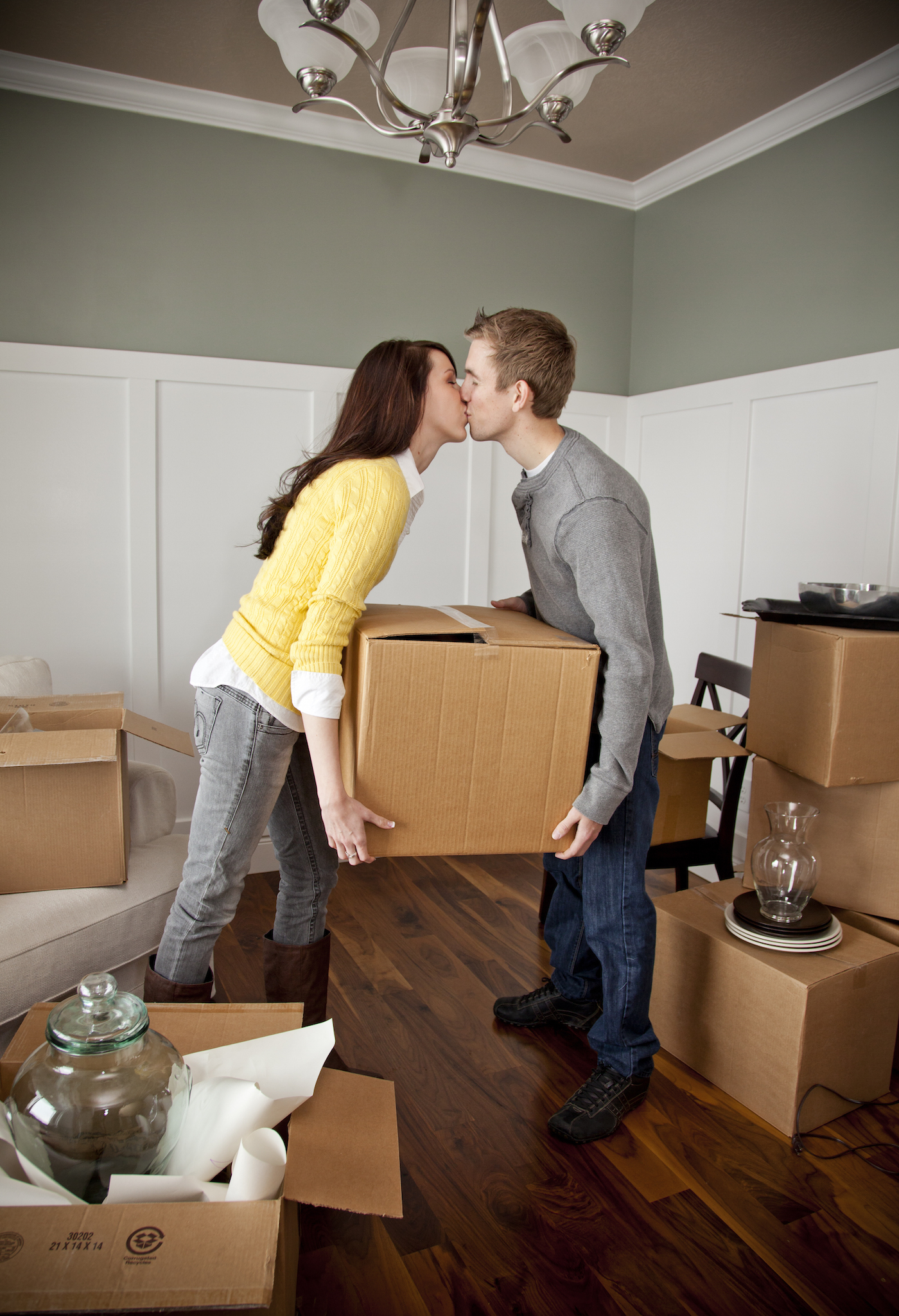 Young couple kissing while moving boxes into their new home built by McArthur Homes