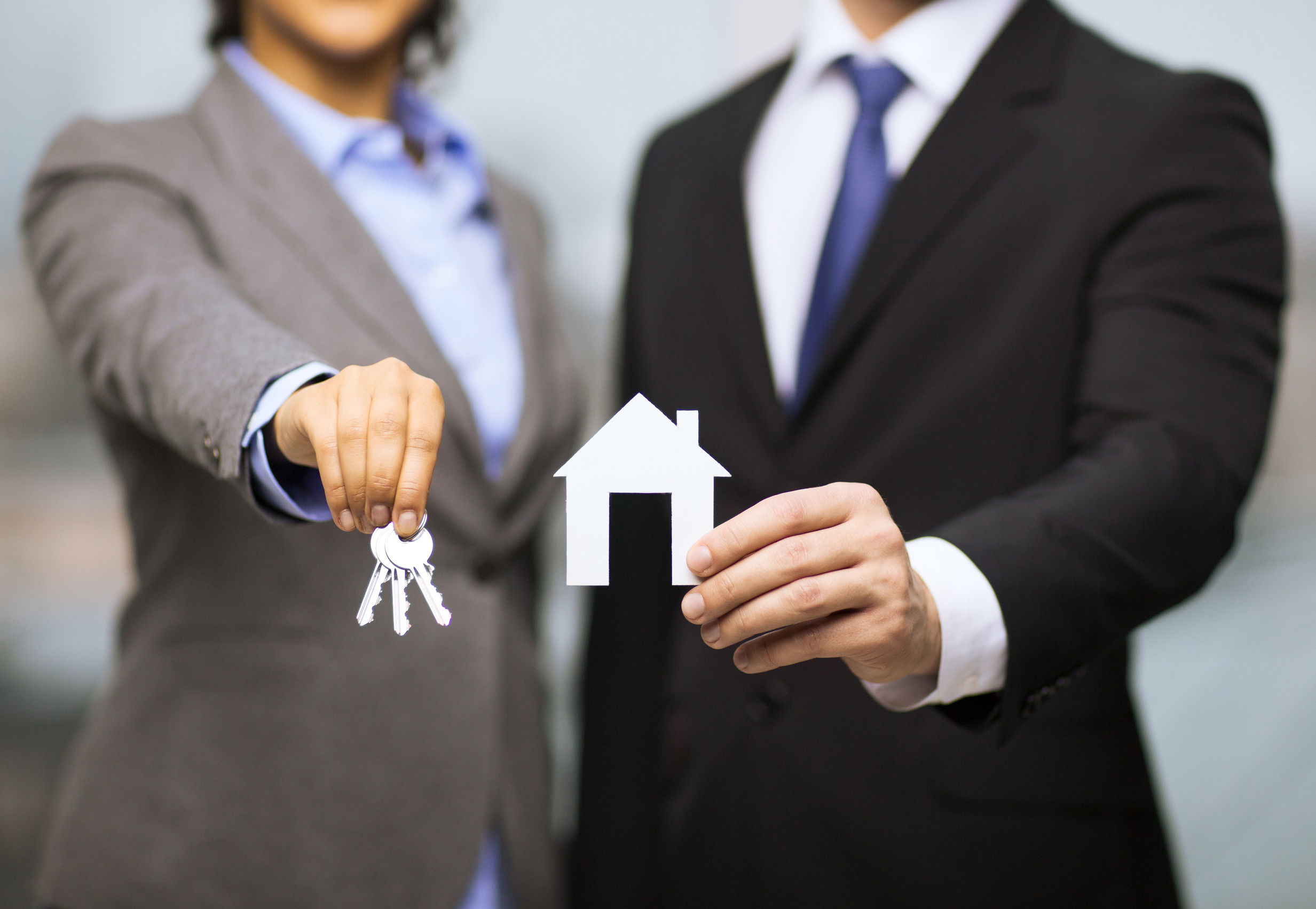 two real estate agents holding keys and house cutout