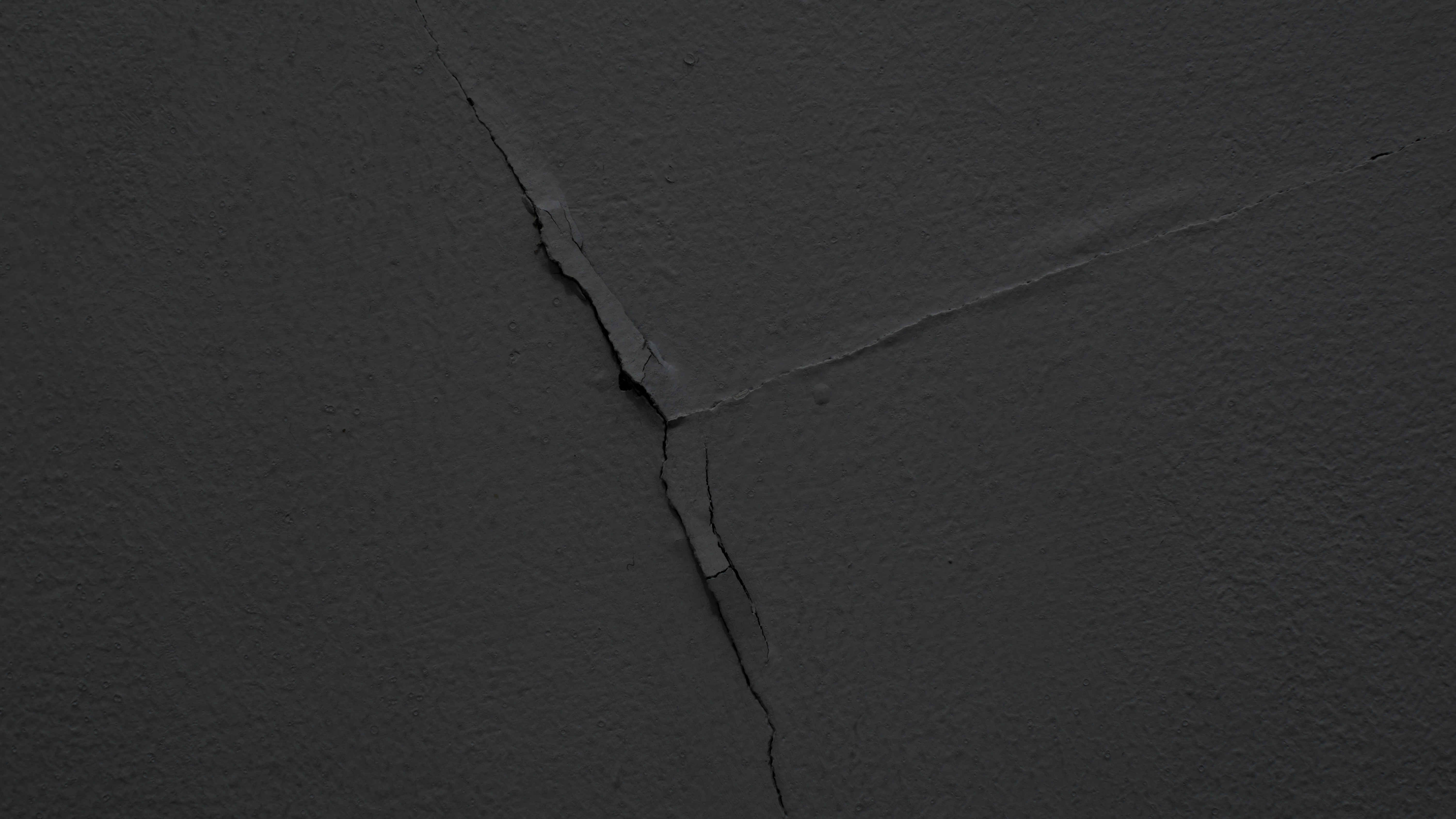 Black wall with a crack running through it